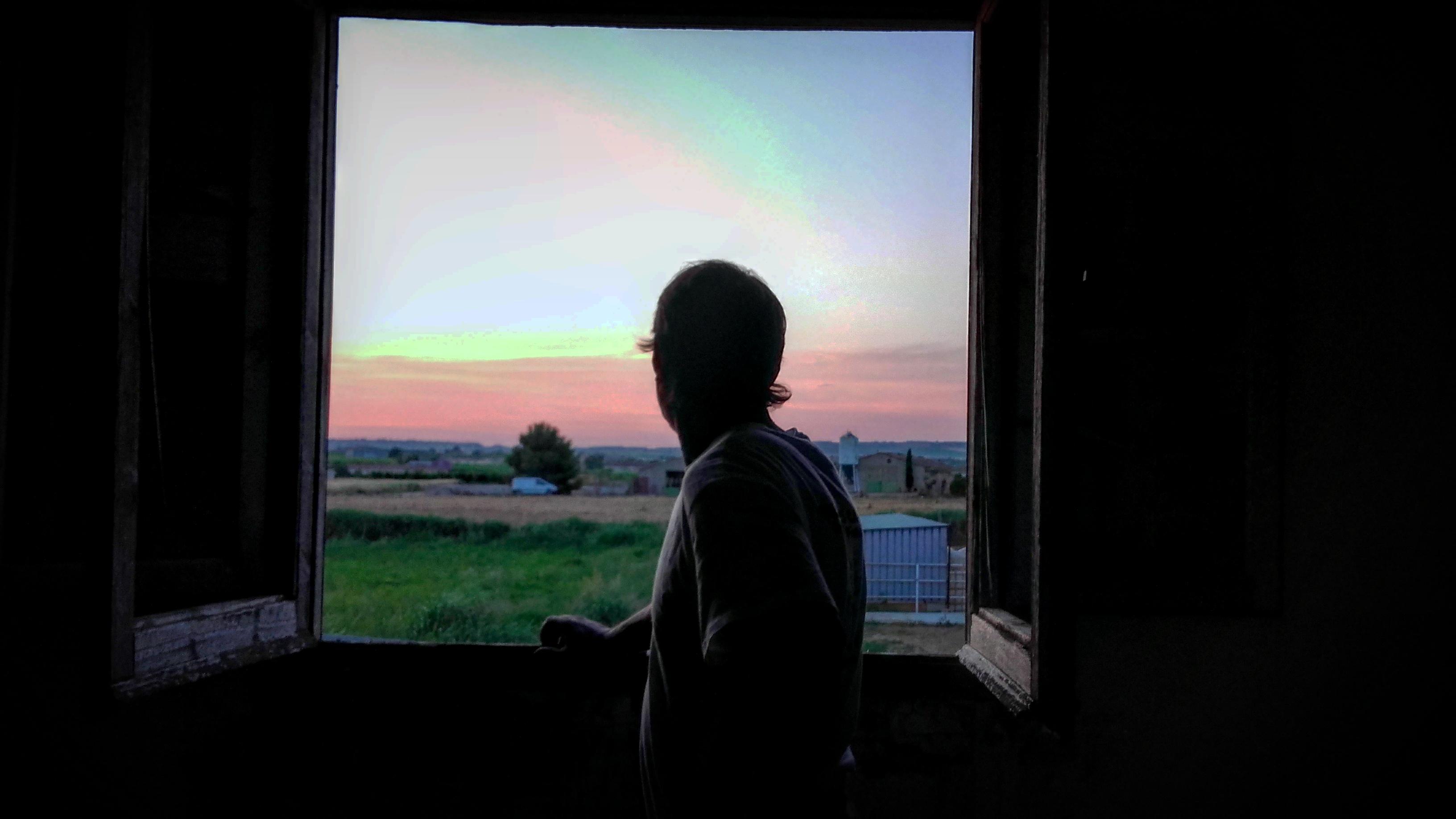 hombre mira por la ventana
